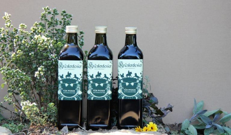 3 Flaschen des Pferdehustensaftes Kräuterelexiers vom Lindenkreuz stehen nebeneinander in einem Beet mit Heilkräutern. Von links her kommt ein Sonnenstrahl.