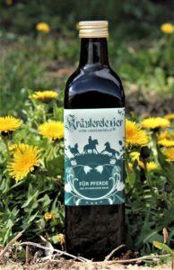 eine Flasche des Pferdehustensaftes Kräuterelexier vom Lindenkreuz gegen Atemwegserkrankungen beim Pferd auf einer Wiese mit Löwenzahn.